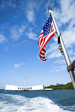 American flag fluttering with a memorial building in the background, Pearl Harbor, Honolulu, Oahu, Hawaii Islands, USA