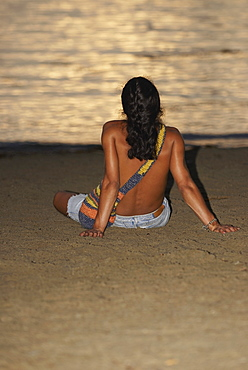 Rear view of a man sitting on the beach, Taganga Bay, Departamento De Magdalena, Colombia