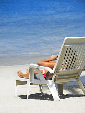Rear view of a woman lying on a lounge chair on the beach, South West Bay, Providencia, Providencia y Santa Catalina, San Andres y Providencia Department, Colombia