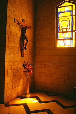 Statue of Jesus Christ on a wall with a flower vase on the floor in a basilica, Basilica Of The Annunciation, Nazareth, Israel
