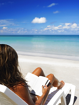 Woman sitting on a lounge chair and reading a book on the beach, Providencia, Providencia y Santa Catalina, San Andres y Providencia Department, Colombia