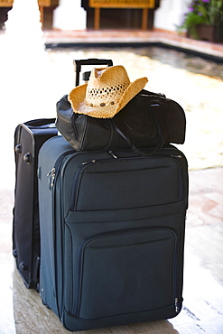 Close-up of a hand bag and a straw hat on a suitcase at the poolside, Cancun, Mexico