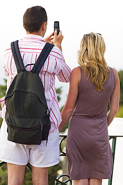 Rear view of a mid adult couple taking photographs with a mobile phone, Capri, campania, Italy