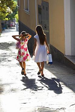 Rear view of two girls walking in a street, Capri, Campania, Italy