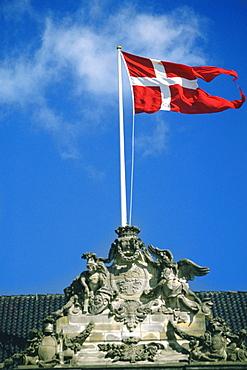 Danish flag fluttering on a sculpture, Amalienborg Palace, Copenhagen, Denmark