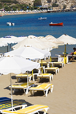 Lounge chairs and beach umbrellas on the beach, Lindos, Rhodes, Dodecanese Islands, Greece