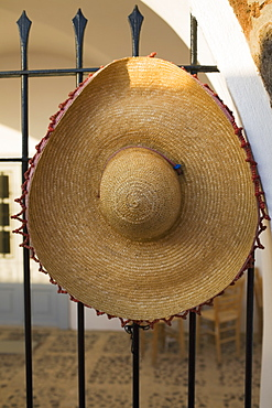 Close-up of a straw hat on a metal fence, Greece