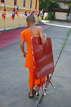 Rear view of a monk carrying a folded table and walking on the road, Vientiane, Laos