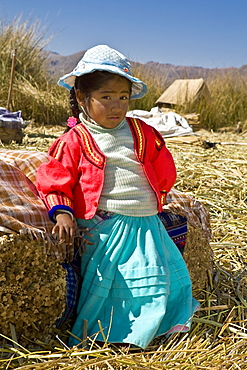 Portrait of a girl leaning against a bale of straw