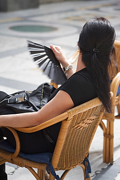 Side profile of a woman sitting on chair and holding a folding fan, Naples, Naples Province, Campania, Italy