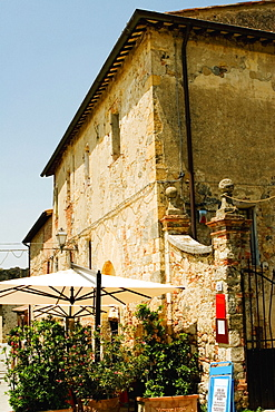 Potted plants and patio umbrellas in front of a building, Piazza Roma, Monteriggioni, Siena Province, Tuscany, Italy