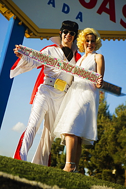 Mid adult man and a mid adult woman dressed in costumes, Las Vegas, Nevada, USA