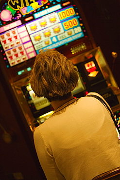 Rear view of a woman sitting in front of slot machine, Las Vegas, Nevada, USA