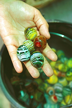 Close-up of a person's hand holding marbles