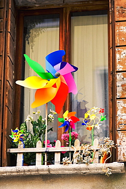 Low angle view of pinwheels with flower vases in front of a window