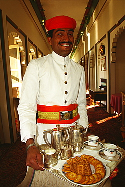 Portrait of a waiter holding a tray and smiling, Fateh Prakash Palace, Udaipur, Rajasthan, India