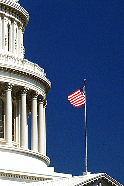 Low angle view of an American flag fluttering on a government building, Capitol Building, Washington DC, USA
