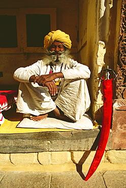 Portrait of a senior man sitting at a veranda of a museum, Meherangarh Museum, Jodhpur, Rajasthan, India