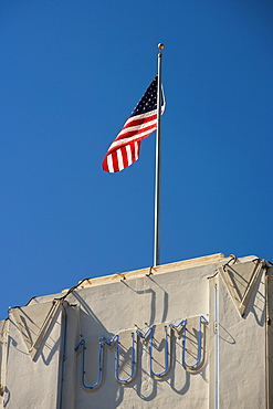 Low angle view of an American flag fluttering on top of a building