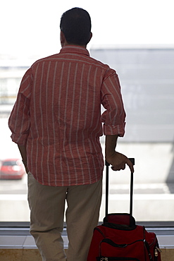 Rear view of a man standing and holding a bag, Madrid, Spain