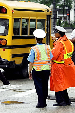 Rear view of two crossing guards standing beside a school bus, Chicago, Illinois, USA