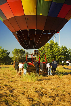 Rear view of people pulling hot air balloon