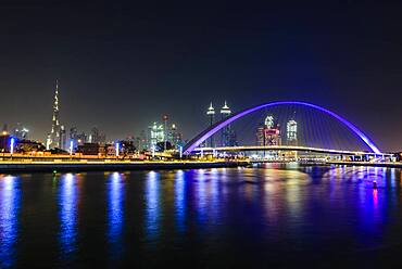 Night, cityscape of Dubai, tall buildings and waterfront, and arch over the creek.
