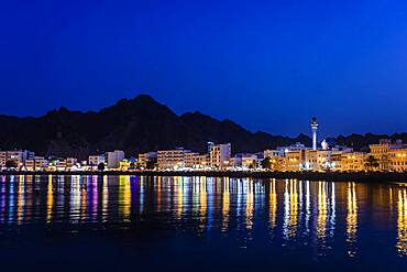 The city of Muscat, waterfront lights, mountains behind, at night
