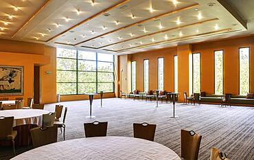 Large empty room in a hotel or conference centre, tables and chairs.