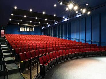 Empty auditorium, rows of raked seats.