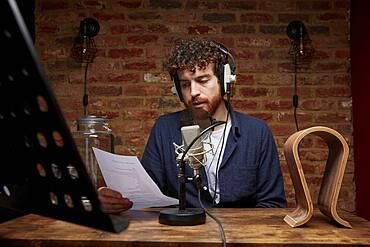 Man wearing headphones reading, speaking into microphone