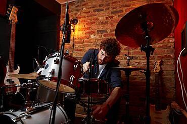 Man adjusting drum set in music studio