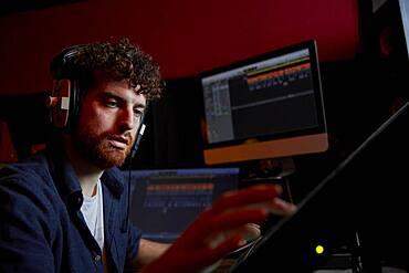 Man working in music studio using computer wearing head phones