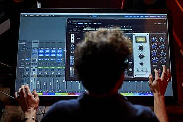 Man working in music studio using large computer screen shot from behind