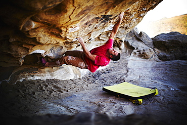 A man free climbing on the overhang of a rock face, with minimum equipment, USA