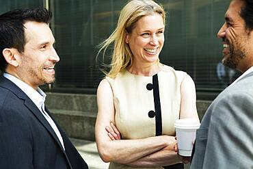 Businesswoman and two businessman standing outdoors, chatting and smiling, New York, United States of America