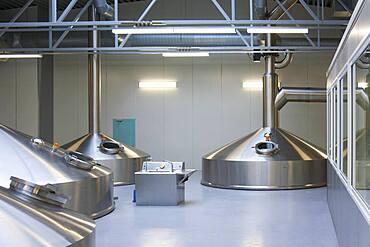 Interior of brewery, large steel storage tanks for brewing beer.
