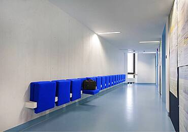 Long corridor in modern training college with blue seats.