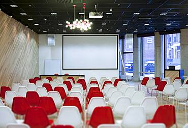 Large empty room with red and white chairs in rows