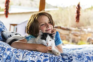 Young boy lying on outdoor bed stroking a pet cat