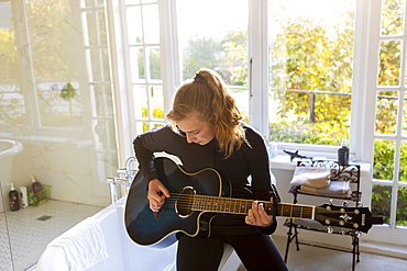 Teenage girl seated on the edge of a bathtub, playing accoustic guitar.