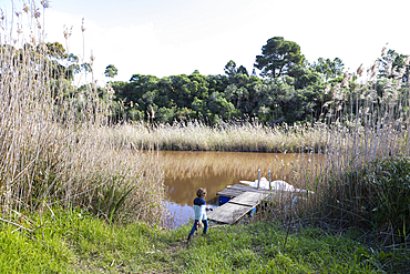 Young boy playing near a lagoon on the Klein River estuary, boat moored at a dock