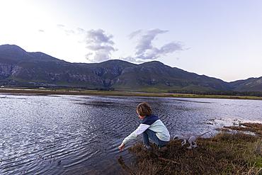A boy exploring the shore of a lagoon in the shadow of the Kleinriver mountain range