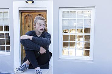 Teenage girl sitting cross legged on a low wall outside a house