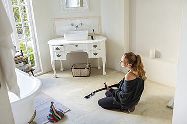 Teenage girl sitting on the floor playing a guitar
