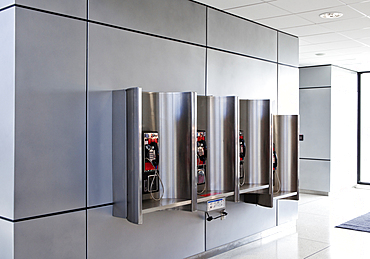A row of public telephones in booths at an airport.