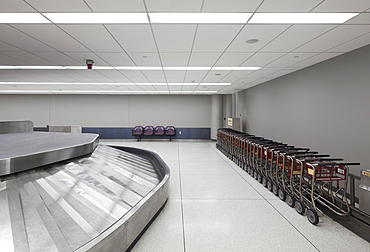 Empty airport luggage claim area, carousels and trolleys.