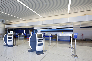 Self check-in desks and traditional baggage check in desks in an empty airport.
