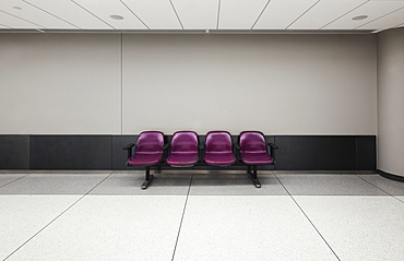 A row of four fixed seats in an empty airport