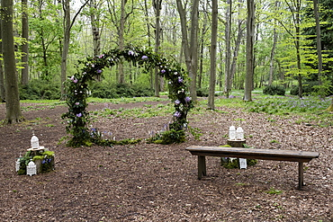 Arch with pink flower decorations for a woodland naming ceremony.